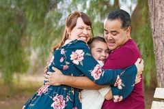 Mixed Race Young Family Hugging At The Park royalty free stock image