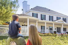 Mixed Race Young Family Looking At Beautiful Home Royalty Free Stock Photo