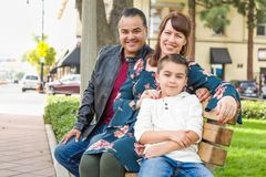 Mixed Race Young Family Portrait on a Park Bench. Mixed Race Young Family Portrait At The Park royalty free stock photo