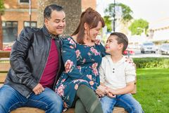 Happy Mixed Race Young Family Portrait on a Park Bench. Mixed Race Young Family Portrait At The Park stock photo