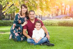 Mixed Race Young Family Portrait At The Park. Mixed Race Young Family Portrait in the Grass At The Park royalty free stock photo