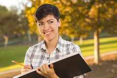 Mixed Race Young Female Holding Sketch Book and Pencil Outdoors Stock Photography