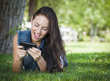 Mixed Race Young Female Texting on Cell Phone Outside Stock Photo