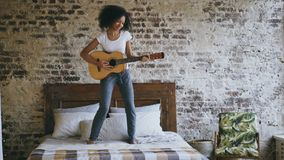 Mixed race young funny girl playing acoustic guitar and have fun dancing on bed at home royalty free stock images