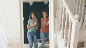 Mixed race young funny girls dance singing with hairdryer and comb in front of mirror. Sisters having fun leisure in stock footage