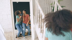 Mixed race young funny girls dance singing with hairdryer and comb in front of mirror. Sisters having fun leisure in. Bedroom at home stock video