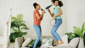 Mixed race young funny girls dance singing with hairdryer and comb jumping on sofa. Sisters having fun leisure in living stock photo