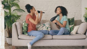 Mixed race young funny girls dance singing with hairdryer and comb sitting on sofa. Sisters having fun leisure in living