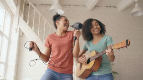 Mixed race young funny girls dance singing with hairdryer and playing acoustic guitar on a bed. Sisters having fun