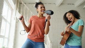 Mixed race young funny girls dance singing with hairdryer and playing acoustic guitar on a bed. Sisters having fun. Leisure in bedroom Royalty Free Stock Photos