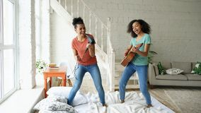 Mixed race young funny girls dance singing with hairdryer and playing acoustic guitar on a bed. Sisters having fun. Leisure in bedroom Royalty Free Stock Images
