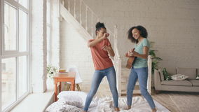 Mixed race young funny girls dancing singing and playing acoustic guitar on a bed. Sisters having fun leisure in bedroom.  stock video
