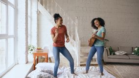 Mixed race young funny girls dancing singing and playing acoustic guitar on a bed. Sisters having fun leisure in bedroom Stock Image