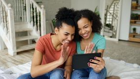 Cheerful mixed race young funny girls talking online video chat on tablet computer with their friends at home. Mixed race young funny girls talking on skype on Stock Photo