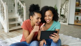 Cheerful mixed race young funny girls talking online video chat on tablet computer with their friends at home. Mixed race young funny girls talking on skype on Royalty Free Stock Images