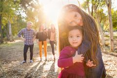 Mixed Race Young Girl Sisters Outdoors with Family Behind. Them royalty free stock photo