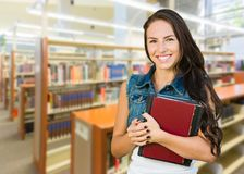 Mixed Race Young Girl Student with School Books Inside Library stock photo