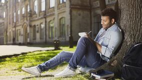 Mixed-race young guy sitting under tree, taking notes in notebook, inspiration. Stock footage Royalty Free Stock Image