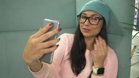 Mixed race young hipster woman makes selfie with coffee while sitting in cafe stock footage