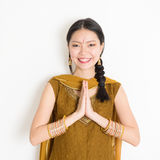 Mixed race young Indian woman greeting. Portrait of young mixed race Indian Chinese girl in traditional punjabi dress with greeting pose, standing on plain white Royalty Free Stock Photo
