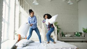 Mixed race young pretty girls jumping on bed and fight pillows having fun at home. Mixed race young pretty girls jumping on bed and fight pillows having fun Royalty Free Stock Images