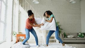 Mixed race young pretty girls jumping on bed and fight pillows having fun at home. Mixed race young pretty girls jumping on bed and fight pillows having fun Royalty Free Stock Photography