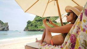 Mixed Race Young Tourist Woman Taking Smartphone Selfie Picture Relaxing on Lounge Bed near Sea on Tropical Island. Girl stock video