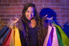Mixed Race Young Woman Holding Shopping Bags Against Brick Wall Stock Photography