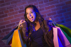 Mixed Race Young Woman Holding Shopping Bags Against Brick Wall Royalty Free Stock Images