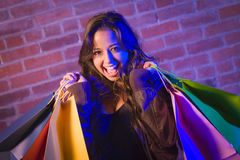 Mixed Race Young Woman Holding Shopping Bags Against Brick Wall Stock Image