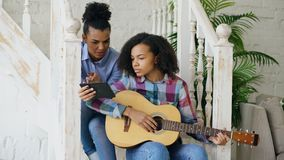 Mixed race young woman sitting on stairs teaching her teenage sister to play acoustic guitar at home Royalty Free Stock Photography