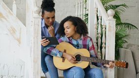Mixed race young woman sitting on stairs teaching her teenage sister to play acoustic guitar at home Royalty Free Stock Photo