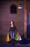 Mixed Race Young Woman Walking Carrying Shopping Bags at Night Royalty Free Stock Photos