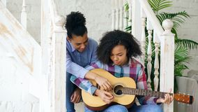 Mixed race young woman sitting on stairs teaching her teenage sister to play acoustic guitar at home Stock Photo