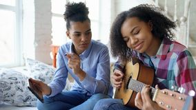 Mixed race young woman with tablet computer sitting on bed teaching her teenage sister to play acoustic guitar at home Stock Photography