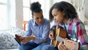 Mixed race young woman with tablet computer sitting on bed teaching her teenage sister to play acoustic guitar at home Royalty Free Stock Images