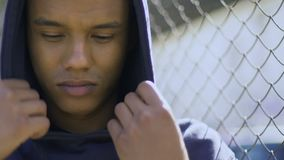 Mixed-raced boy wrapping in hood staying alone, suffering from bullying, racism. Stock footage stock video footage
