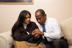 Mixed Raced Christian Couple Praying Together. At Home Sitting on Couch royalty free stock photo