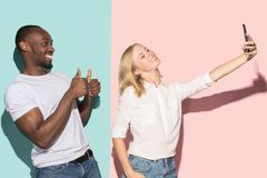 Mixed raced couple of students taking common selfie with phone. Caucasian girl and her African boyfriend posing at. Studio . Communication and relationship stock photo
