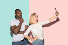 Mixed raced couple of students taking common selfie with phone. Caucasian girl and her African boyfriend posing at. Studio . Communication and relationship royalty free stock photography