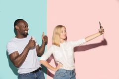 Mixed raced couple of students taking common selfie with phone. Caucasian girl and her African boyfriend posing at. Studio . Communication and relationship stock photography
