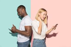 Mixed raced couple of students taking mobile phones. Caucasian girl and her African boyfriend posing at studio . Mixed raced couple of students taking mobile stock photography