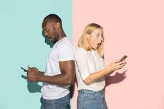 Mixed raced couple of students taking mobile phones. Caucasian girl and her African boyfriend posing at studio . Mixed raced couple of students taking mobile royalty free stock photography