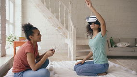 Mixed raced woman using virtual reality glasses while her friend holding digital tablet computer. Girlfriends play video stock video footage