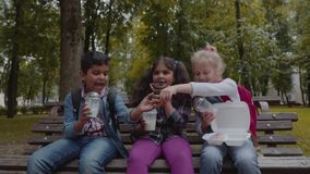 Mixed Racial Group of school kids eating lunch together on break outdoors near school. Back to school concept. Slow. Group of school kids eating lunch together stock video