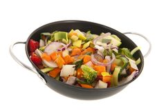 Mixed vegetables in frying pan. Mixed raw vegetables in frying pan isolated over white background Stock Image