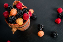 Mixed of red, black, yellow raspberries in a basket on  wooden background. Close up. Top view. Copy spase. Stock Photos