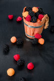 Mixed of red, black, yellow raspberries in a wooden basket and berry on black table. Close up. Stock Photo