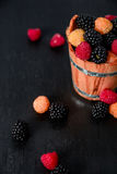 Mixed of red, black, yellow raspberries in a wooden basket and berry on  table. Close up. Stock Photos