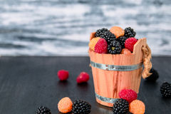 Mixed of red, black, yellow raspberries in a wooden basket and berry on  table. Close up. Royalty Free Stock Photography